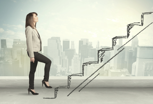Businesswoman climbing a staircase on a city background